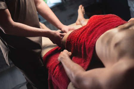 Male professional sports massage of the hip and knee in a dark massage room. premium massage services. Copy space