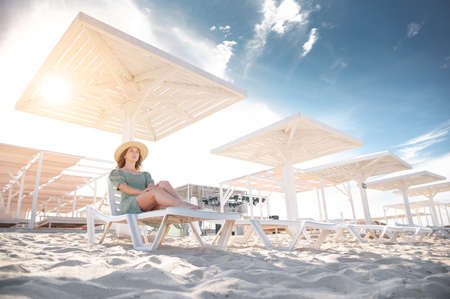 Young caucasian woman in a green dress and straw hat sits on a sun lounger under a wooden umbrella on a white sandy beach by the sea. Copy space. tourism and recreation in hot countries