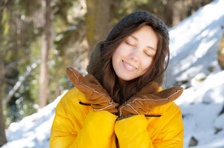 Happy young caucasian woman in a winter down jacket hat and mittens with eyes closed with happiness rejoices spreading her hands in a winter coniferous forest Foto de archivo