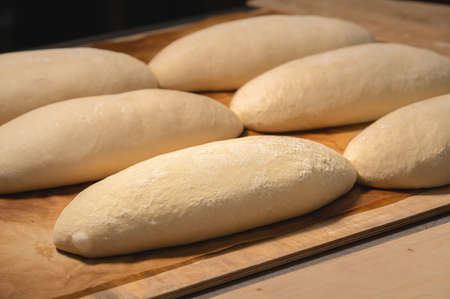 Several loaves of raw dough lie on a wooden board. Craft bread before baking
