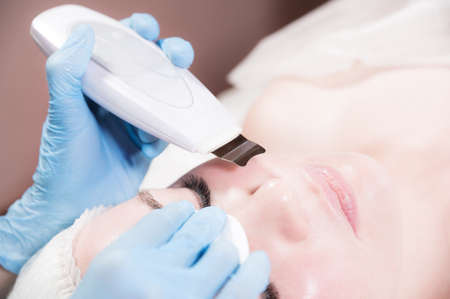 Close-up Professional face cleaning. Mechanical ultrasonic face cleansing procedure. Peeling of the skin of the face. Foto de archivo