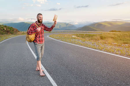 Smiling bearded friendly caucasian man in a shirt and shorts with a backpack greets you by raising his hat while standing on a country road high in the mountains at sunset