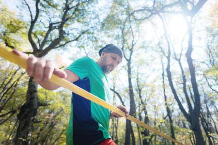 Portrait of a man slackliner next to a stretched slack in the autumn forest. Copy space for slack events