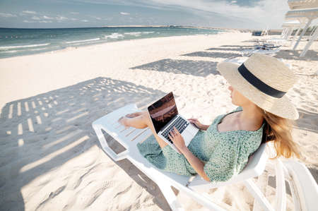 Morning beach Young Caucasian woman in dress and straw hat uses her laptop while sitting on the sandy beach by the sea at sunset. Freelancer and remote work in warm countries Foto de archivo