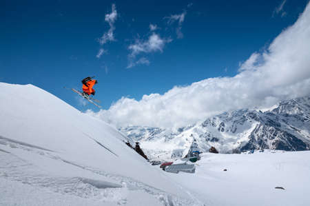 Athlete skier freestyle jumping in orange ski suit in snowy mountains on a sunny day Foto de archivo