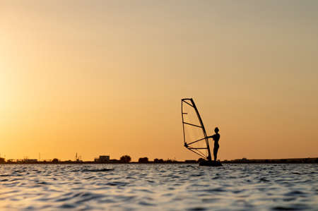 Silhouette of a young woman kitesurfer at sunset. Trainings in calm weather on the estuary Foto de archivo