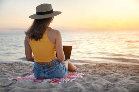 Back view Young caucasian woman in shorts and a straw hat uses her laptop while sitting on the sandy beach by the sea at sunset. Freelancer and remote work