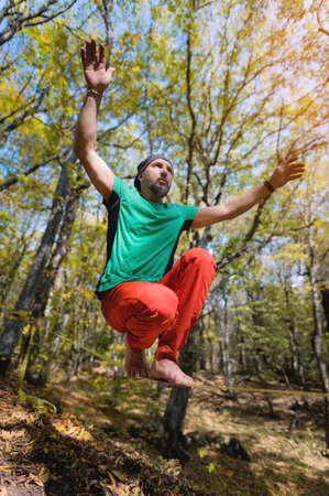 Mature male athlete doing a sitting trick while standing on the slackline. Sports activities to develop balance in the autumn outdoor forest