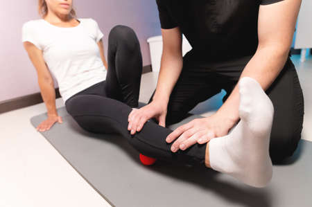 Physiotherapist teaches self-massage with red balls, patient with leg injury. Treatment of sports injuries. Practical use. Rehabilitation concept.