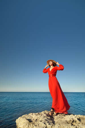 Lovely romantic caucasian young woman in red dress and straw hat