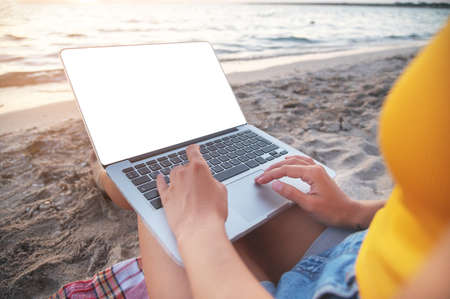 Close-up of a cut-out laptop screen on the lap of a young caucasian woman sitting on a sandy beach by the sea at sunset. Freelance and remote work presentation copy space Foto de archivo