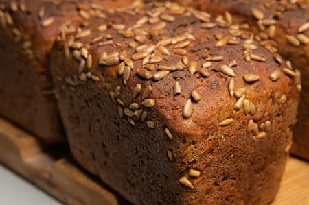fresh brown loaves of rye bread in the form of bricks with sunflower seeds on a crust. Lie on a wooden rack Foto de archivo