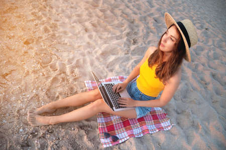 Young caucasian woman in shorts and a straw hat uses her laptop while sitting on the sandy beach by the sea at sunset. Freelancer and remote work
