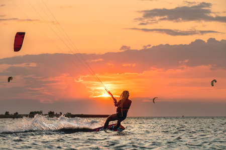 Young woman professional kiter performs ride beautiful background of the sunset and sea
