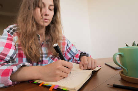 Young woman sitting at the kitchen table makes notes in a notebook. Home Office. Caucasian girl being homeschooled Foto de archivo
