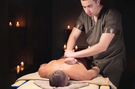a professional masseur a physiotherapist makes a back massage to a client man in a dark room of a massage room by candlelight Foto de archivo