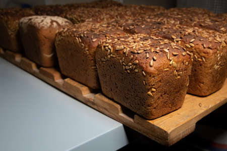 Close-up fresh brown loaves of rye bread in the form of bricks with sunflower seeds on a crust. Lie on a wooden rack Foto de archivo
