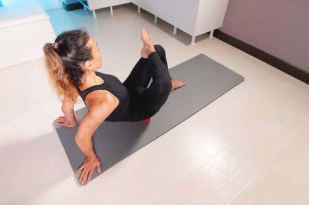 Athletic caucasian slim woman doing myofascial self-massage of the thigh and gluteus muscles in a massage room