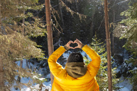Back portrait young caucasian woman and shows fingers gesture of heart, love at eye level. Back view in forest
