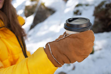 Close-up paper cup with a black lid in the hands of a woman in mittens