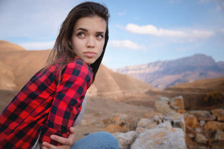 Portrait of attractive caucasian young woman enjoying in the mountains against the background of epic rocks looking away