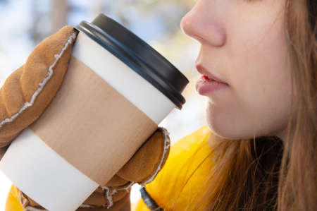 people, season, drinks and leisure concept - close up of woman hand with coffee cup outdoors in winter