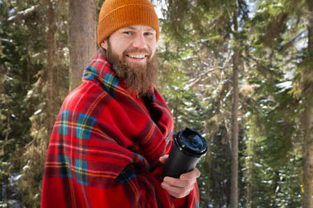 Happy bearded caucasian young man in a hat and plaid with a paper black cup laughing and looking at the camera in a winter coniferous forest in the afternoon