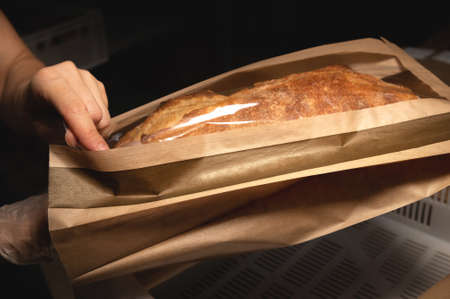 Womens caring hands pack fresh artisan bread in a paper bag with a transparent insert. Craft bread packaging
