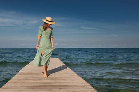 An attractive young Caucasian woman in a green dress and a straw hat is walking lightly on a wooden pier on a sunny day against the backdrop of the sea. Rest and walks by the ocean