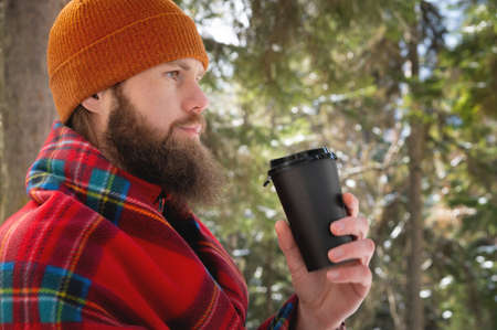 Bearded caucasian man in a hat wrapped in a blanket with a mug of hot drink in a paper cup in a winter coniferous forest on a sunny day Foto de archivo