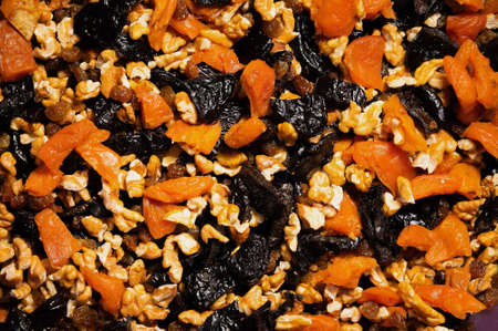Dried mixture of walnuts and dried fruits, raisins, grapes and prunes close-up. Mix for adding to baked goods or appetizers. Healthy vegan food Foto de archivo