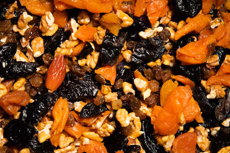 Dried mixture of walnuts and dried fruits, raisins, grapes and prunes close-up. Mix for adding to baked goods or appetizers. Healthy vegan food Banque d'images