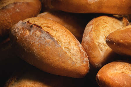 Close-up of sourdough bread. Freshly baked bread with a golden crust on the wooden shelves of the bakery. The context of a German artisan bakery with an assortment of rustic breads.