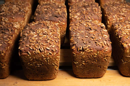 Close-up fresh brown loaves of rye bread in the form of bricks with sunflower seeds on a crust. Lie on a wooden rack Banque d'images