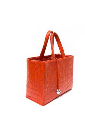 Orange leather handbag with crocodile texture isolated on white Stock Photo