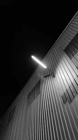 Street photography of outdoor wall lamp brighten up over the metal sheet wall of construction site in the middle of the night