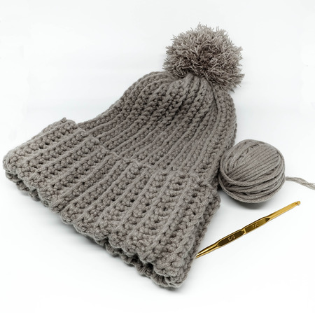 Gray crochet hat, yarn ball and golden needle Stok Fotoğraf