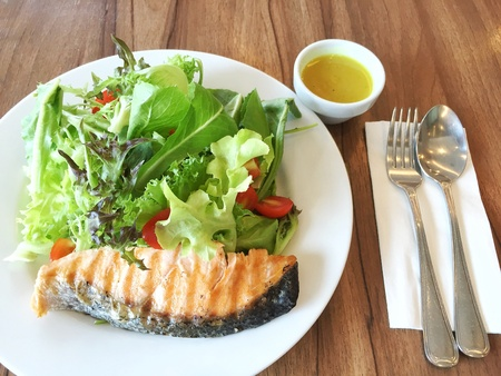 spoon and fork: Yummy healthy grilled salmon salad with salad dressing and spoon fork Stock Photo