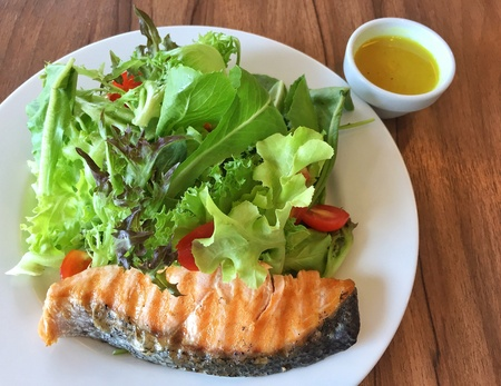 up: Yummy healthy grilled salmon and salad dressing in close up