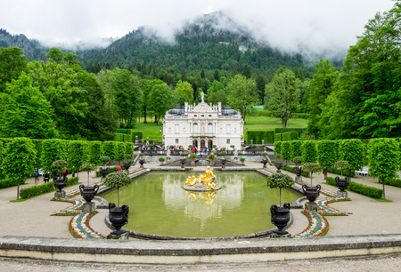 ludwig: Ettal, Germany-June 11, 2016: Linderhof palace and fountain in garden, one of palace that King Ludwig II owned and finished when he was alive. Photo was shot on raining cloudy day.