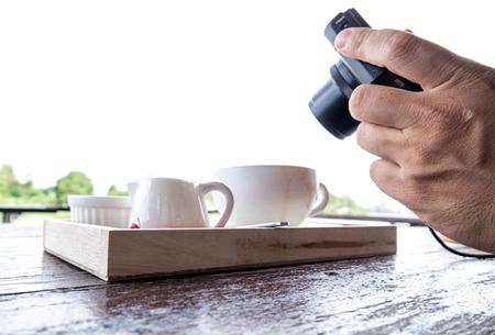 handholding: A man taking photo of coffee set.  Handholding camera shooting food shot. Outdoor day time.