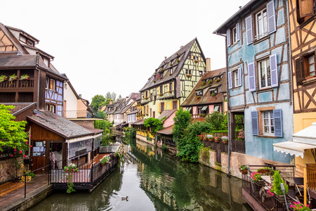 Canal and colorful houses in Petite Venice, Colmar, France. View from bridge in cloudy day.