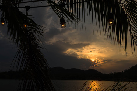 Silhouette of mountain and lake in evening time with light bulb lines. Mood and tone at sundown.