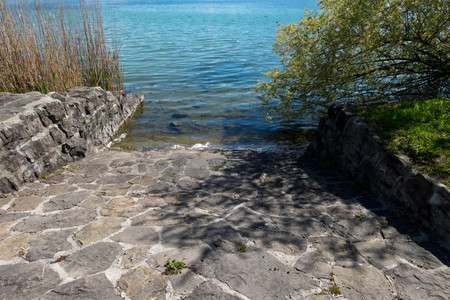 Rock-made path down to clear lake water.