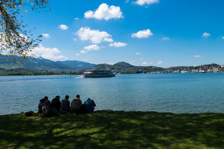 May 5, 2017 - Lucern, Switzerland: friends relax and spend holiday by lake on nice weather day. Editorial