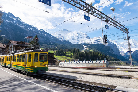 May 12, 2017 - Lauterbrunnen, Switzerland: train about to stop at Wengen station. Alps and nature as beautiful background of it.