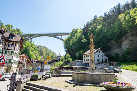 May 10, 2017 - Fribourg, Switzerland: a part for cityscape of Fribourg town. Dry fountain with old soldier holding flag at toll.