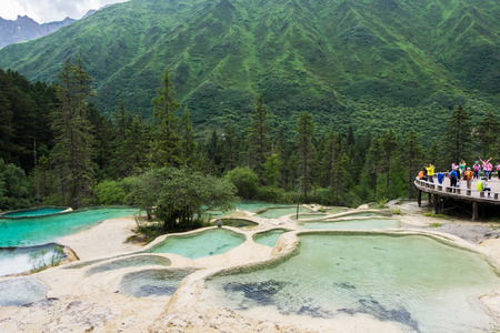 Jul 16, 2017 - Sichuan, China: Scenic spot with travelers at Guests welcome pond in Huanglong park. People were stunned by the amazing natural beauty.