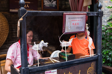 Jul 20, 2017 - Chengdu, China: Sugar candy art made by a woman behind bar in Jinli Pedestrian Street in Chengdu. It is a handmade work which is rarely to see nowsaday.