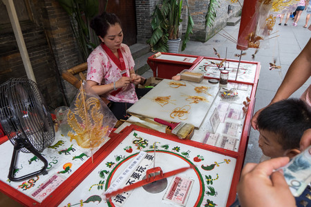 Jul 20, 2017 - Chengdu, China: Sugar candy art made by a woman behind bar in Jinli Pedestrian Street in Chengdu. A boy chooses design by spinning wheel and get a candy art in 10 yuan.